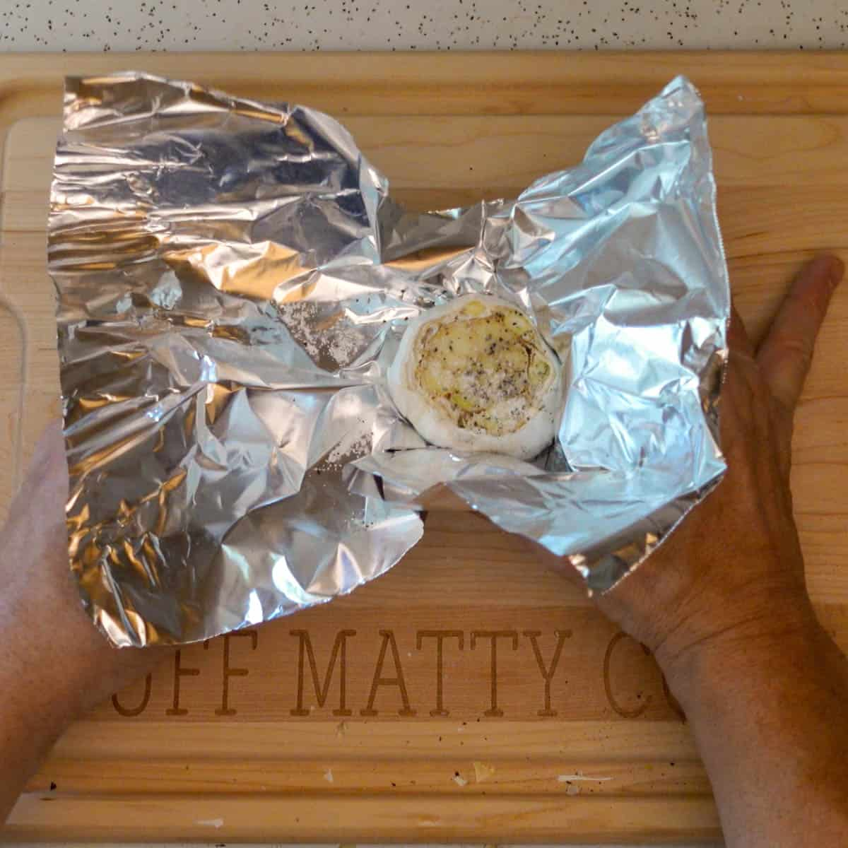 roasted garlic getting wrapped in foil for roasting