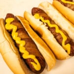 Bacon wrapped hot dog ready to eat with some yellow mustard
