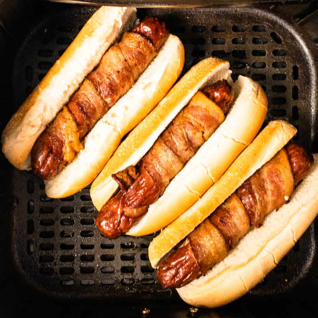 bacon wrapped hotdogs in bun in airfryer basket to toast bun
